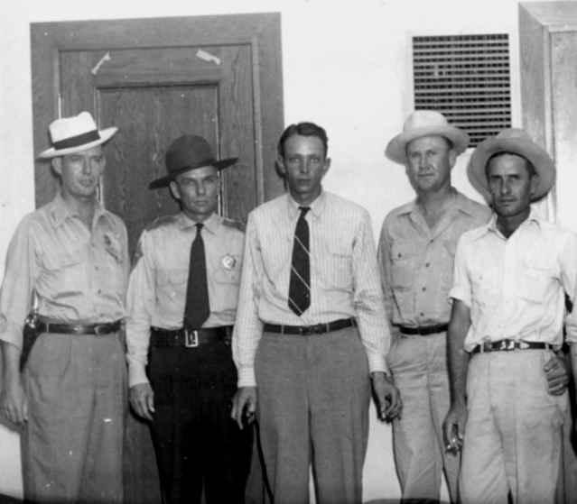 Йоуел Суини (в средата) и арестувалите го офицери
